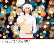Купить «smiling woman in santa hat opening christmas gift», фото № 27062807, снято 15 августа 2013 г. (c) Syda Productions / Фотобанк Лори