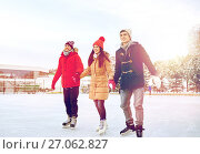 Купить «happy friends ice skating on rink outdoors», фото № 27062827, снято 22 декабря 2014 г. (c) Syda Productions / Фотобанк Лори