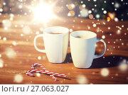 Купить «christmas candy canes and cups on wooden table», фото № 27063027, снято 1 октября 2015 г. (c) Syda Productions / Фотобанк Лори