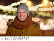 Купить «happy young man over christmas lights in winter», фото № 27063127, снято 2 декабря 2016 г. (c) Syda Productions / Фотобанк Лори