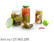 Pickled cucumbers, peas, carrots, pepper in jars and pickled cucumbers on a plate close-up on a white background. Стоковое фото, фотограф Татьяна Ляпи / Фотобанк Лори