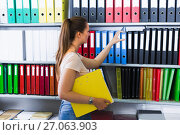 Купить «Woman is choosing folders on the shelves», фото № 27063903, снято 9 мая 2017 г. (c) Яков Филимонов / Фотобанк Лори