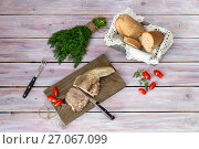Sliced veal tongue on a cutting board with dill, tomatoes and bread on a wooden table close-up. Стоковое фото, фотограф Татьяна Ляпи / Фотобанк Лори