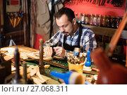 Купить «Male worker working on leather for belt in leather», фото № 27068311, снято 24 февраля 2019 г. (c) Яков Филимонов / Фотобанк Лори