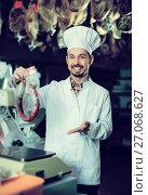 Купить «Smiling male seller weighing on scales sausage», фото № 27068627, снято 2 января 2017 г. (c) Яков Филимонов / Фотобанк Лори