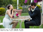 Купить «Bridegroom photographing bride blowing kiss while sitting at table in park», фото № 27069123, снято 2 мая 2017 г. (c) Wavebreak Media / Фотобанк Лори