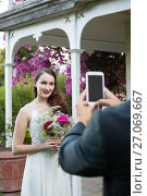 Купить «Cropped hands of bridegroom photographing bride at park», фото № 27069667, снято 2 мая 2017 г. (c) Wavebreak Media / Фотобанк Лори