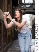 Купить «Young female tourist is taking photo on her phone», фото № 27073731, снято 17 мая 2017 г. (c) Яков Филимонов / Фотобанк Лори