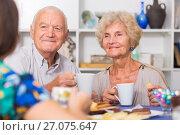 Купить «Smiling elderly spouses enjoying tea with girl», фото № 27075647, снято 28 августа 2017 г. (c) Яков Филимонов / Фотобанк Лори