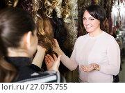 Купить «Two customers purchasing hair extension», фото № 27075755, снято 17 октября 2018 г. (c) Яков Филимонов / Фотобанк Лори
