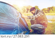 Купить «happy male traveler setting tent up outdoors», фото № 27083291, снято 27 сентября 2015 г. (c) Syda Productions / Фотобанк Лори