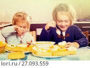 Купить «Children eat cakes at kitchen», фото № 27093559, снято 14 декабря 2018 г. (c) Яков Филимонов / Фотобанк Лори