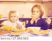 Купить «Two little girls enjoying pastry with cream», фото № 27093563, снято 14 декабря 2018 г. (c) Яков Филимонов / Фотобанк Лори