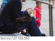 Купить «Man uses mobile phone outdoor, telephoto», фото № 27103551, снято 3 октября 2017 г. (c) Константин Шишкин / Фотобанк Лори