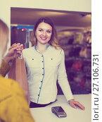 Купить «Woman seller is handing numerous purchases to client», фото № 27106731, снято 20 марта 2017 г. (c) Яков Филимонов / Фотобанк Лори