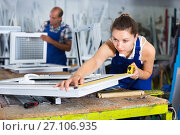 Купить «Female worker measuring finished metal-plastic window in workshop», фото № 27106935, снято 19 июля 2017 г. (c) Яков Филимонов / Фотобанк Лори