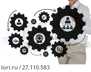 Business woman interacting with people in cogs graphics against office background. Стоковое фото, агентство Wavebreak Media / Фотобанк Лори