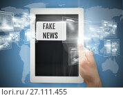 Купить «Holding tablet with Fake news text and interface», фото № 27111455, снято 21 мая 2018 г. (c) Wavebreak Media / Фотобанк Лори