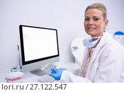 Купить «Portrait of dentist working while sitting by computer», фото № 27122547, снято 11 декабря 2016 г. (c) Wavebreak Media / Фотобанк Лори