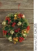 Купить «Christmas wreath hanging on wooden background», фото № 27124255, снято 8 июня 2017 г. (c) Wavebreak Media / Фотобанк Лори