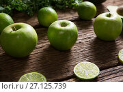 Купить «Green apple and sliced lemon arranged on wooden table», фото № 27125739, снято 12 июня 2017 г. (c) Wavebreak Media / Фотобанк Лори