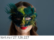 Купить «Woman wearing masquerade mask against black background», фото № 27126227, снято 22 мая 2017 г. (c) Wavebreak Media / Фотобанк Лори