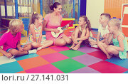 Купить «Kids sitting around teacher with small guitar», фото № 27141031, снято 23 мая 2019 г. (c) Яков Филимонов / Фотобанк Лори