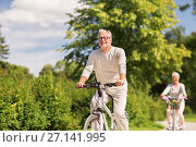 Купить «happy senior couple riding bicycles at summer park», фото № 27141995, снято 9 августа 2017 г. (c) Syda Productions / Фотобанк Лори
