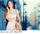 Купить «happy woman talking on phone and standing in old town», фото № 27142751, снято 26 августа 2017 г. (c) Яков Филимонов / Фотобанк Лори