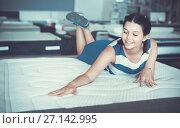 Купить «Female is lying on mattress for testing it in the store.», фото № 27142995, снято 29 августа 2017 г. (c) Яков Филимонов / Фотобанк Лори