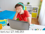 Купить «boy in headphones playing video game on laptop», фото № 27145051, снято 10 июня 2017 г. (c) Syda Productions / Фотобанк Лори