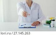 Купить «doctor showing medicine cup with pills at hospital», видеоролик № 27145263, снято 21 июля 2018 г. (c) Syda Productions / Фотобанк Лори