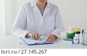 Купить «doctor putting pills into medicine cup at hospital», видеоролик № 27145267, снято 16 августа 2018 г. (c) Syda Productions / Фотобанк Лори