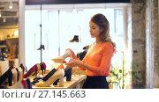 Купить «happy young woman choosing shoes at store», видеоролик № 27145663, снято 6 октября 2017 г. (c) Syda Productions / Фотобанк Лори