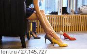 Купить «young woman trying heeled shoes at store», видеоролик № 27145727, снято 6 октября 2017 г. (c) Syda Productions / Фотобанк Лори