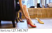 Купить «young woman trying heeled shoes at store», видеоролик № 27145767, снято 6 октября 2017 г. (c) Syda Productions / Фотобанк Лори