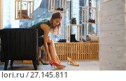 Купить «young woman trying heeled shoes at store», видеоролик № 27145811, снято 6 октября 2017 г. (c) Syda Productions / Фотобанк Лори