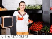 Купить «Female customer examining various tomatoes», фото № 27148843, снято 23 ноября 2016 г. (c) Яков Филимонов / Фотобанк Лори