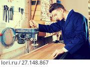 Купить «Man laying board to drill», фото № 27148867, снято 7 ноября 2016 г. (c) Яков Филимонов / Фотобанк Лори