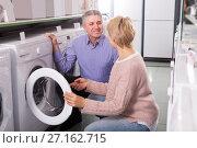 Купить «friendly mature couple chooses washing machine for their house in shop of household appliances», фото № 27162715, снято 27 марта 2019 г. (c) Яков Филимонов / Фотобанк Лори