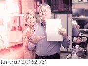 Купить «Mature couple buying on credit agreement for home appliances», фото № 27162731, снято 21 июля 2019 г. (c) Яков Филимонов / Фотобанк Лори