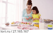 Купить «mother and daughter cooking cupcakes at home», видеоролик № 27165167, снято 27 марта 2019 г. (c) Syda Productions / Фотобанк Лори