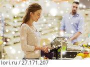 Купить «woman buying food at grocery store cash register», фото № 27171207, снято 21 октября 2016 г. (c) Syda Productions / Фотобанк Лори