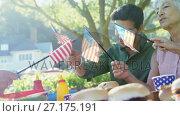 Купить «Family holding american flags during meal in the park 4k», видеоролик № 27175191, снято 9 апреля 2020 г. (c) Wavebreak Media / Фотобанк Лори