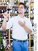Купить «Cheerful man holding glass of red wine in winery section», фото № 27179195, снято 20 октября 2018 г. (c) Яков Филимонов / Фотобанк Лори