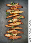 Купить «Slices of baked potatoes with rosemary on a textured stone table.», фото № 27179427, снято 18 июня 2019 г. (c) Olesya Tseytlin / Фотобанк Лори