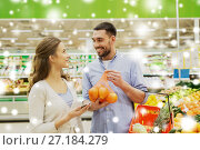 Купить «happy couple buying oranges at grocery store», фото № 27184279, снято 21 октября 2016 г. (c) Syda Productions / Фотобанк Лори