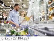 Купить «couple with shopping cart buying food at grocery», фото № 27184287, снято 21 октября 2016 г. (c) Syda Productions / Фотобанк Лори