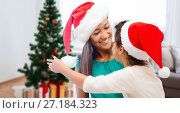Купить «happy mother and daughter in santa hats», фото № 27184323, снято 25 августа 2013 г. (c) Syda Productions / Фотобанк Лори