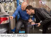 Купить «mechanic and customer looking at car taillight», фото № 27184623, снято 21 сентября 2017 г. (c) Syda Productions / Фотобанк Лори